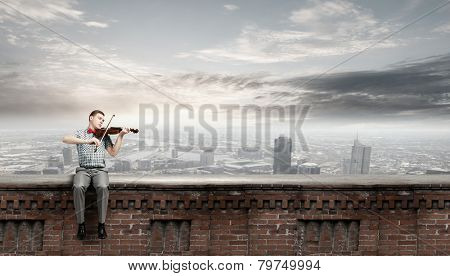 Young handsome man sitting on bench and playing violin