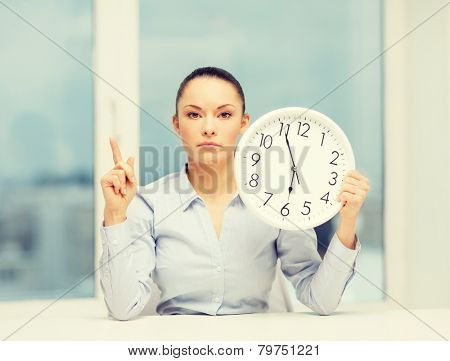 business, office, school and education concept - attractive businesswoman showing clock with finger up