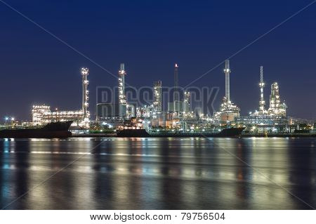 Oil refinery at twilight along with river reflexion