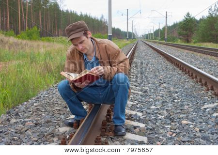 Man Sits On Railway And With Reads