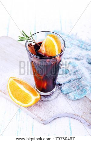 Glass of hot mulled wine with pieces of orange on cutting board with mittens and color wooden table background