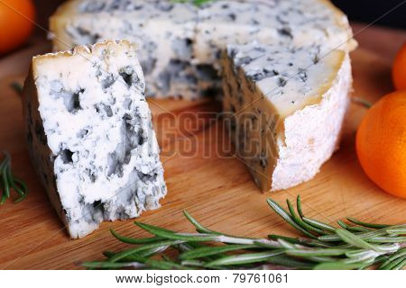 Blue cheese with sprigs of rosemary and orange on wooden board background
