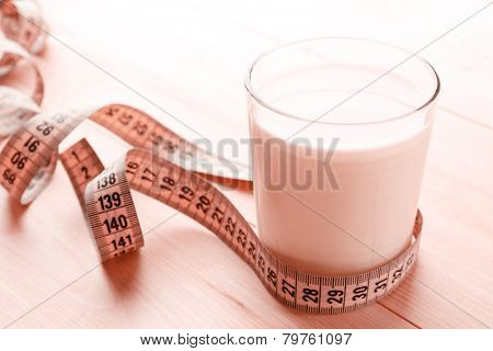 Glass of dietary cocktail with measuring tape on wooden table background