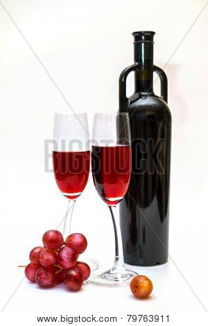 Rare Red Wine Bottle, Red Grapes And Two Wine Glasses On The White Background