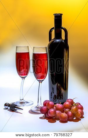 original red wine bottle, grapes and two wine glasses on a colorful background