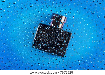 Bottle Of Cologne Through Water Drops On Glass