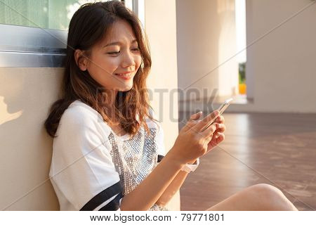 Portrait Of Beautiful Young And Teen Woman Looking To Mobile Phone With Smiling Face In Home Outdoor