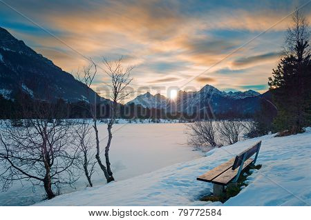 lonely park bench at sunset in alps with frozen lake in winter