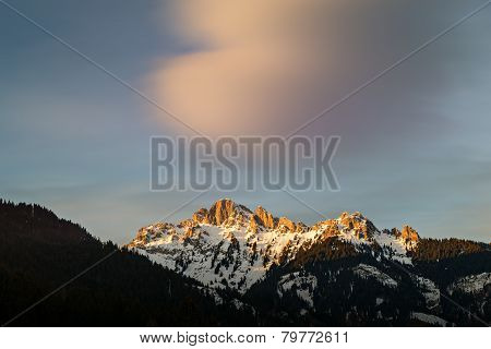 afterglow of evening sun in tirol alps at winter with big cloud