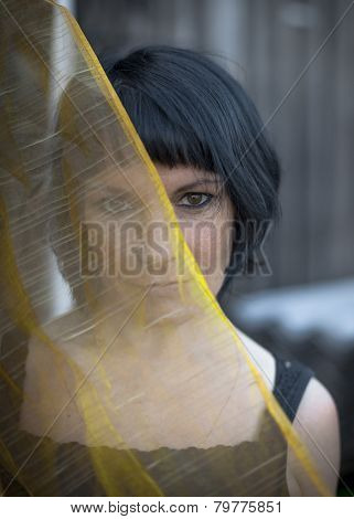 Portrait of a woman outdoors, half of the face is covered by translucent veil.