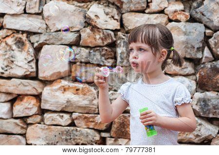Lovely Little Girl Blowing Soap Bubbles