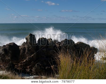 Waves smash in on rocky coast.