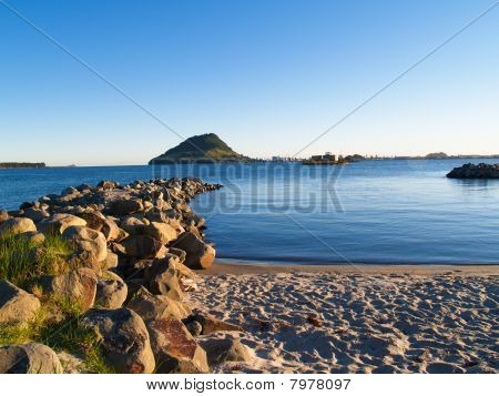 Beach, harbour and mount on horizon.
