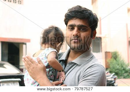 Indian father smiling and holding his baby