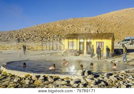 TERMAS DE POLQUES, BOLIVIA, MAY 17, 2014: Tourists take bath in hot springs in the middle of Sur Lipez desert
