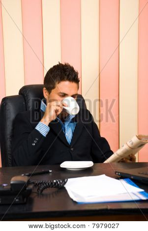 Corporate Man Reading News And Drinking Coffee