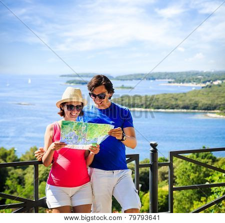 Couple Looking at Map by the Sea