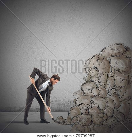 Businessman digs to remove an obstacle rock