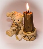 stock photo of inflamed  - A Nice inflamed candle with ceramic bear sitting - JPG
