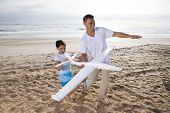 Hispanic Dad, Girl Playing With Toy Plane On Beach