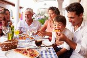 stock photo of grandparent child  - Multi Generation Family Eating Meal At Outdoor Restaurant - JPG
