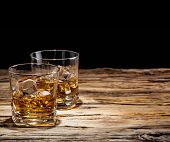 foto of whiskey  - Whiskey drinks on wooden table with black background - JPG