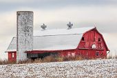 stock photo of red barn  - An old red barn with basketball hoop and silo stands in a snowy field on a cloudy day - JPG