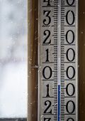 foto of freezing temperatures  - Close up of the temperature gauge on the window and flying snowflakes across the image bad weather concept - JPG