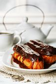 stock photo of eclairs  - Tasty eclairs and cup of tea on wooden table - JPG