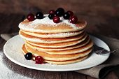 stock photo of dessert plate  - Stack of delicious pancakes with powdered sugar and berries on plate and napkin on wooden background - JPG