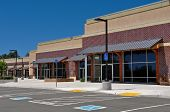 stock photo of commercial building  - New Brick Strip Mall Shopping Center and parking lot - JPG
