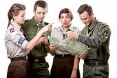 image of boy scouts  - Four young scout members in uniform looking to the map and compass isolated on white background - JPG