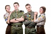 stock photo of boy scout  - Four young scout members embracing in uniform isolated on white background - JPG
