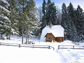 stock photo of chalet  - Scenery of small wood chalet over snow - JPG