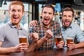 stock photo of cheers  - Three happy young men in casual wear holding glasses with beer and cheering while watching football match in bar together - JPG