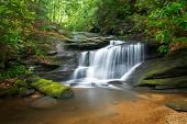 stock photo of backwoods  - Motion Blur Waterfalls Peaceful Nature Landscape in Blue Ridge Mountains with lush green trees rocks and flowing water - JPG