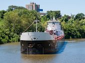 stock photo of iron ore  - a Great Lakes self discharging bulk carrier laden with iron ore sails up the Cuyahoga River headed for a steel mill in Cleveland - JPG