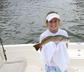 stock photo of redfish  - Photograph of a young girl holding a freshly caught redfish in a towel so as not to get her hands fishy - JPG