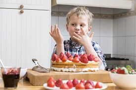 foto of finger-licking  - Cute boy licking his fingers with batter - JPG