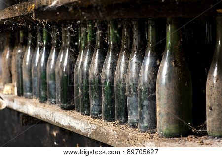 Old Dusty Wine Bottles On A Cellar Shelf