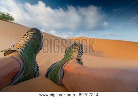 Feet of the hiker relaxing in the desert