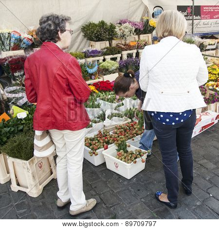 Woman Buy Flowers From Market Stall In The Netherlands