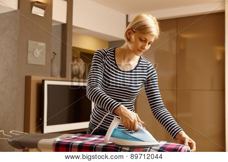 Young woman ironing in living room at home.