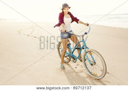 An attractive young woman riding her bicycle on the beach