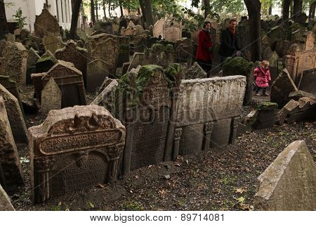 PRAGUE, CZECH REPUBLIC - OCTOBER 15, 2012: People walk among abandoned tombstones at the Old Jewish Cemetery in Prague, Czech Republic.