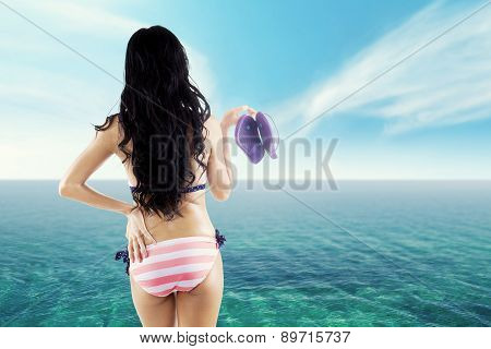 Woman Holds Flip-flops At Coast