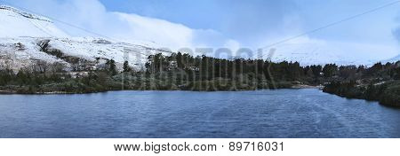 Panorama Winter Landscape Of Lake With Forest And Mountain Range In Background