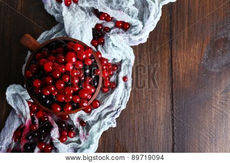 Cup of juicy berries on wooden table with scarf, top view