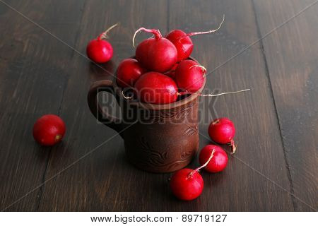 Red radish in clay cup on wooden background