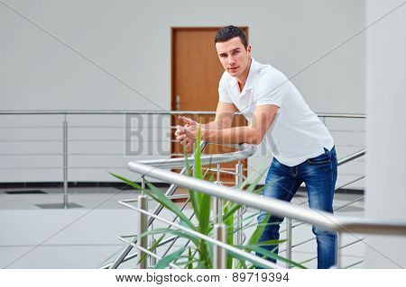 Young Man In A Polo Shirt Stands Leaning On Railing